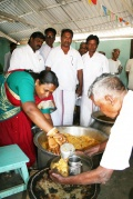 The political leader of the district distribut the meal to the students
