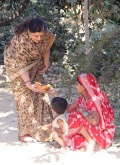 Mrs Raman give a Banana to a child in the colony .JPG