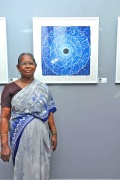 Bindu Artist Maligai stands proudly beside her painting